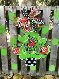 Fun & Funky Christmas Tree Door hanger created from 1/4 wood, hand painted and finished with a vibrant assortment of seasonal ribbon. Please