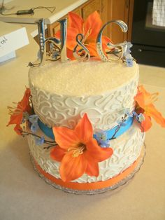 Blue and Orange themed wedding cake! 2 tier stacked with real ribbon, cake topper and artificial flowers provided by client. All buttercream!  http://www.facebook.com/angelas.cakes2011