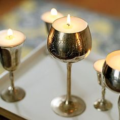 "A set of metal goblets made into a set of elegant votives.    How they did it:  ""We cleaned them with metal polish and a clean cloth. Then we filled them with Microwaveable Soy Wax for Containers and used Pre-Waxed Medium Bleached Wick with Wick Clip to make elegant, long-burning votives"" (old trophies and crystal glasses of all shapes will also do the trick)"