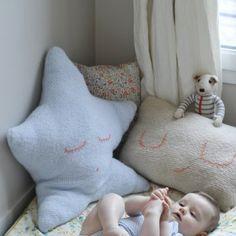 des coussins tricotés pour bébé en forme d'étoile et de frimousse avec des yeux et une bouche brodés.