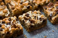 """This bar cookie is an old fashioned favorite. Chocolate chips, nuts and coconut are set in a caramelized layer on top of a graham cracker crust.""  Ingredients     	1/2 cup butter or margarine, melted   	1 1/2 cups"