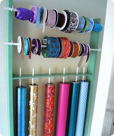 diy wrap and ribbon organizer - if you want wrapping paper to be horizontal just make it wider and drill holes on each side to slip the rods in and out or use the cup hooks.