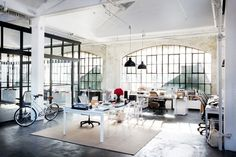 Sewing studio inspiration. Charcoal concrete floors, jute rug. White table. Set Design of Nancy Meyers' The Intern