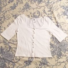 NWT Charlotte Russe Crop Button Front Top New with tags. White cropped button-front top. Scoop neck and half sleeves. Tag says size Medium, but it fits more like a Small. Faux mother-of-pearl buttons. Charlotte Russe Tops Button Down Shirts