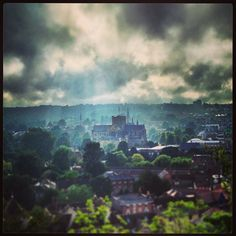 Winchester Cathedral lit up by sun rays on a stormy evening from St Giles Hill.