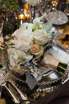 Champagne ribbon and antique roses accent this bouquet of white roses, Calla lilies and dusty miller leaves.