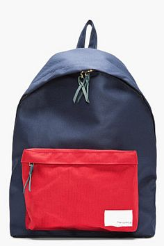 """NANAMICA // NAVY & RED CANVAS BACKPACK 32467M004003  Canvas backpack in navy. Leather trimmings throughout in blue. Gold tone hardware. Single carry handle at top. Two padded adjustable shoulder straps at back. Zip cargo pocket at bag face in red with logo patch in white. Two way zip closure at main compartment. Ivory canvas lining. Tonal stitching. Approx 14"""" length x 17"""" height x 6.5"""" width. 50% cotton, 50% polyester. Cordura fabric. Made in Japan."""