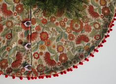 Cheerful vintage Christmas tree skirt packs a punch! Bright heavy upholstery is adorned by a perky red pom pom trim and bronzy-gold, over-sized