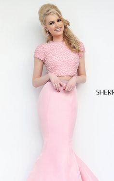 Let all eyes be on you in Sherri Hill 32248. This eye-catching evening gown showcases a high neckline with short sleeves. The back is trimmed with keyhole detailing that creates a figure flattering look. This dress is created with a two piece set dress, with the fabulous mermaid skirt gives a spectacularly dramatic formal look.