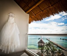 A delicate wedding dress rests on the balcony of a beautiful destination venue.