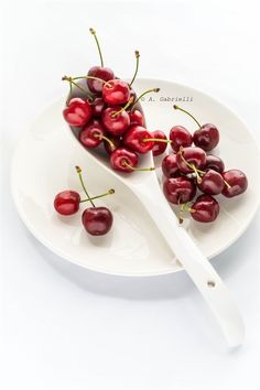 red and white. cherries. white spoon.