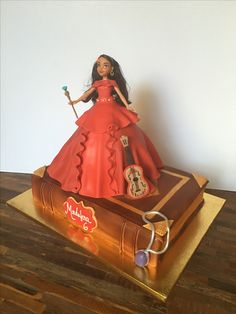 Disney's Elena of Avalor birthday cake. The bottom is a book resembling that found in the intro to the show. Cake also includes her amulet, guitar, and Elena figurine in a cake dress detailed in fondant.