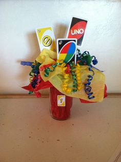 Uno themed centerpieces, canning jar, dowel sticks with uno cards curling ribbon and tissue paper with mini uno card hot glued to jar for easy removal to not ruin jar! Cute cheap and easy!!
