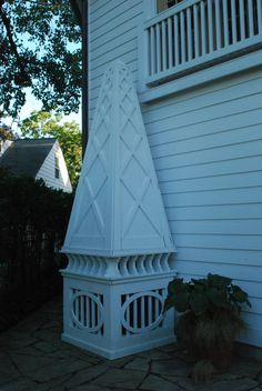 The air conditioner is under this painted wood obelisk, yes. One panel is hinged, and folds down, making service a snap. In the top of the obelisk-long handled gardening tools