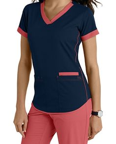 NrG by Barco brings to you this cute scrub top highlighted by contrast banded sleeves, neck and piping details on sides and hem.  Includes three roomy pockets.     V-neck  Three pockets  Fitted back  Contrast details  Medium center back length 26