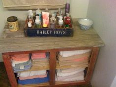 Old barn wood cabinet for towels in bathroom, BUT the main thing is an old wooden crate that is divided to hold all your perfumes, lotions, and ect!!! Looks super cute in the bathroom!!!