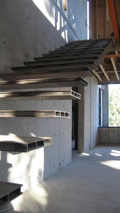 Escalera de diseño volada, de peldaños metálicos. Cantilevered-steel-stair-off-concrete-wall
