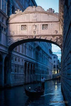 A gondola glides through the canal beneath the Bridge of Sighs in Venice