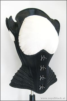 Royalblack Couture corset top made from shiny black satin with external bone casings.  On the hips there are lots of small pieces arranged like ribs and the shoulders and neckline are also accentuated with separate satin pieces - all decorated with black Swarovski crystals. The front closure features black swing hooks.  Price: from 949,00 €*