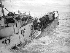 A ' VERY DRAMATIC ' photo from World War Two showing a landing craft gun (medium) (almost certainly LCG (M) 101) crew fighting to save their shell ridden and sinking craft during the landing by Royal Marine commandos on the island of Walcheren at Westkape. Note how everybody is engaged in the effort with no signs of panic when the boat is almost under.