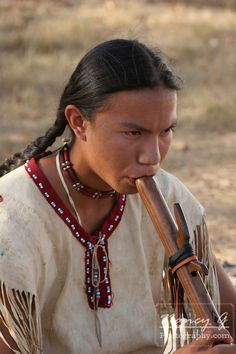 A Native American Teenage Indian Boy Playing A Wooden Handcaved Flute…