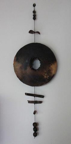 Le disque central est composé de deux disques soudés à leur circonférence et percés en leur centre - diamètre :30 cm . La terre cuite d'abord à 1000 °C est ensuite enfumée dans un container