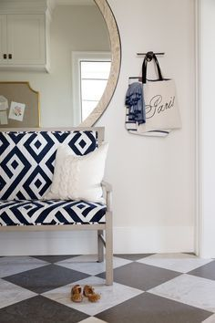An navy and white settee layered in front of an oversized mirror in the mud room. It's perfect to take your shoes on and off and check your makeup before you leave the house. | Designed by Alice Lane | French Moderne Manor