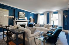 living rooms - glossy blue walls white tufted sofas white black geometric rug blue velvet chairs glass tables mirrored coffee table white drapes gray ribbon trim fireplace blue black faux snake skin console table