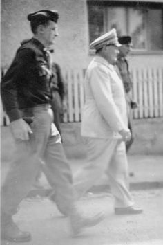 """Herman Goering is escorted by an American serviceman following his capture.     The original caption [partially blurred] reads """"Falstaff Goering is as ugly as he looks. [Note the] sickeningly ingratiating smile -- It won't save him."""""""