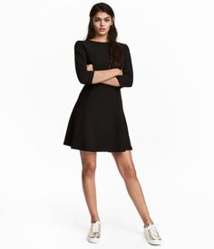 Black. Short dress in ribbed jersey. Opening at back of neck with covered button. 3/4-length sleeves and flared skirt.