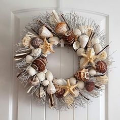 NEWLY DESIGNED 21 SEA SHELL WREATH ON BIRCH TWIG WITH BROWN AND NATURAL COLOR DRIFTWOOD. EMBELLISHED WITH LARGE CROWN SHELLS, ALPHABET TURBO SHELLS, BROWN SCALLOPS, 3 ARMORED STAR FISH, AND A VARIETY OF EXOTIC SHELLS.  INNER DIAMETER - 5 INCHES. STANDS ABOUT 4-5 INCHES FROM ITS BASE.  PERFECT ADDITION TO YOUR ENTRY DOOR AND GREAT WALL DECOR, (see special instructions for outdoor care).  DESIGNED AND ASSEMBLED BY ELLIES COLLECTIONS, ETC. OCEANSIDE, CA. MADE IN USA.  SAFE SHIPPING GUARANTEED…
