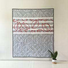 This modern, gender-neutral baby quilt features red and light gray hand-drawn pistachios, scattered across a solid gray and striped background. This is a whole cloth quilt!