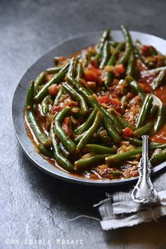 Middle Eastern Spiced Green Beans with Olive Oil and Tomato (Loubieh bil Zayt) is a dish that's simple to make, but complex in flavor. This dish is heady with aromatic spices, onion, and garlic, an… Middle East Food, Middle Eastern Dishes, Middle Eastern Recipes, Middle Eastern Vegetarian Recipes, Comida Siciliana, Lebanese Recipes, Lebanese Green Beans Recipe, Armenian Recipes, Lebanese Cuisine