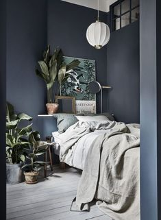 Gorgeous Scandinavian style bedroom with dark great walls, linen bedding and lots of house plants!