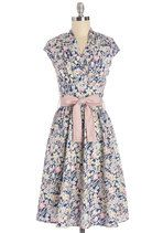 Whether you're traveling on a Parisian getaway or just daydreaming of one, you'll love greeting your companions in this printed frock! This dress captures the romantic feel of vintage stills of butterflies and daffodils in a host of ecru, pink, and blue hues. With its mauve-pink sash around its gently gathered waist, its wrap-style, V-shaped neckline, and cap sleeves, this beautiful number earns your stamp of approval!