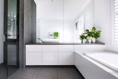 Designed by Canny Architecture this single family home in Malvern East features this family bathroom is spacious with white cabinetry and dark tiled surfaces, with a separate powder room, perfect for larger families. #canny #bathroom #design