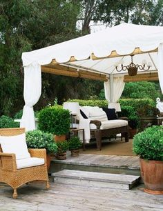 White gazebo with roll-up bamboo shades and sisal rug