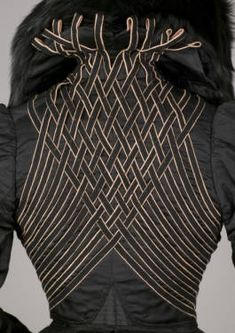 Ensemble, 1900. Suit of black ribbed silk. Jacket (a), waist-length, with wide collar, trimmed in fox fur, left front button closure, and long puffed sleeves, trimmed with panels of black and yellow wool. Monsieur LaFerrière, Paris.