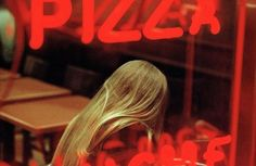 """Constantine Manos, A young woman in a pizza parlor, Times Square, New York City, 2005 """