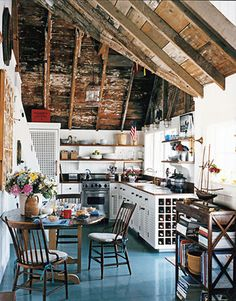 Things I love about this photo: Rough, unfinished wood. Wine storage. Cookbook bookshelf. Blue floor. Bright white cabinets. So bright and airy. Flowers on the table.