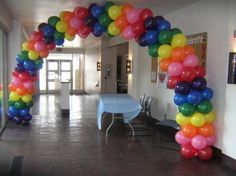 Rainbow Balloon arch to welcome guests to Care-a-lot!  Care Bears Birthday Party :)
