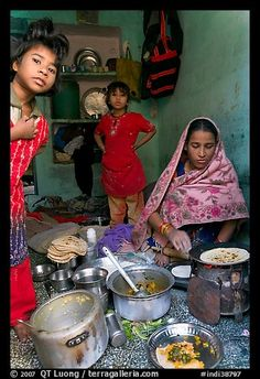 Woman cooking, flanked by two girls. Jodhpur, Rajasthan, India
