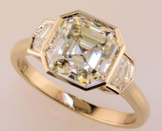 """Idée et inspiration Bague Diamant : Image Description Look at this unusual engagement ring! A gorgeous Asscher cut diamond is flanked by """"Cadillac cut"""" diamonds and set in raw white gold. Unusual Engagement Rings, Vintage Engagement Rings, Diamond Engagement Rings, Unusual Rings, Asscher Cut Diamond, Diamond Cuts, Bling Bling, Bijoux Art Deco, Gold Wedding Rings"""