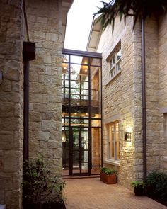Two story glass walls create a dramatic contemporary entry to this old-world style home.