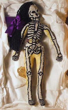 'Gran Brigitte' is one of the Loa of Haitian Voodoo and wife to Baron Samedi, a Loa of the dead.    Doll made of leather, selected objects (within), beads and purple ribbon.  Height 25cm/ 10 in    From my personal collection, 1996