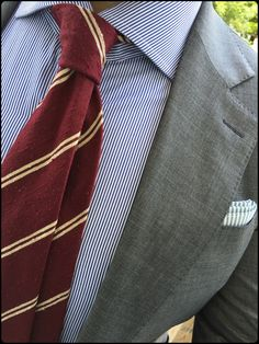 Light grey jacket, white shirt with blue pinstripes, red tie with cream stripes