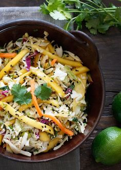 Light, fresh and crisp healthy slaw recipe made with shredded cabbage, carrots, lime juice, rice vinegar and a slightly under-ripe mango topped with sesame seeds.