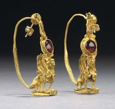 A PAIR OF GREEK GOLD AND GARNET EARRINGS HELLENISTIC PERIOD, CIRCA 2ND-1ST CENTURY B.C. Each in the form of a sphinx standing on a rectangular plinth, her wings upraised, the feathers detailed with twisted wire, adorned with a diadem and twisted wire bands that cross her chest and wrap around the tops of her forelegs, centered by a circular bezel between the breasts, the stone now missing, the tips of the wings joined to an oval bezel with a twisted wire fringe, set with a cabochon garnet, t