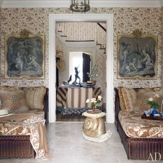 Alex Papachristidis.  The loggia's Cowtan & Tout wall covering serves as a backdrop for two 18th-century grisaille paintings, each hanging above a Bielecky Brothers wicker daybed with cushions of a Clarence House fabric.