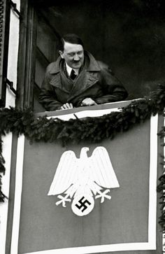 Absolutely a 10 of a photo. This is Garmisch-Partenkirchen in February, 1936 during the winter Olympics. He's leaning out of his hotel room at the Olympia Haus. Here's a photo of him exiting the place